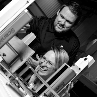 Un enseignant et une étudiante observant une machine